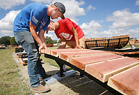 NWA Arkansas Democrat-Gazette/DAVID GOTTSCHALK Austin Fullerton (left) and Trevor Brown, both installers with Progressive Bike Ramps, brace Tuesday, September 11, 2018, a section of a Nessy 3 Bump feature at the Runway Bicycle Skills Park at the Jones Center in Springdale. The park will have the largest asphalt pump track in North America and will host the Pump Track (bicycling) World Championships sponsored by Red Bull in October.