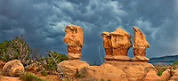 920750007 panoramic view -  lightning flashes behind the four trolls red rock formations during a summer thunderstorm in devils garden escalante grand staircase national monument utah united states
