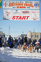 Ray Redington Jr. and team leave the ceremonial start line at 4th Avenue and D street in downtown Anchorage during the 2014 Iditarod race.<br /> Photo by Jim R. Kohl/IditarodPhotos.com