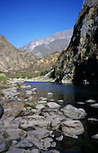 Apurimac Valley, Peru. Wide Apurimac river with rounded boulders and rocks and steep valley sides around.