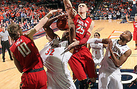 Virginia forward Darion Atkins (32) is fouled by Maryland guard/forward Jake Layman (10) and Maryland center Alex Len (25) during the game Sunday in Charlottesville, VA. Virginia defeated Maryland in overtime 61-58. Photo/Andrew Shurtleff