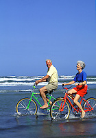 A laughing senior couple rides their bikes on the beach.