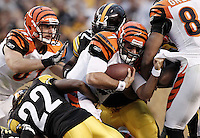 PITTSBURGH, PA - DECEMBER 04:  Bruce Gradkowski #7 of the Cincinnati Bengals hangs onto his teammate while being tackled by the Pittsburgh Steelers defense during the game on December 4, 2011 at Heinz Field in Pittsburgh, Pennsylvania.  (Photo by Jared Wickerham/Getty Images)
