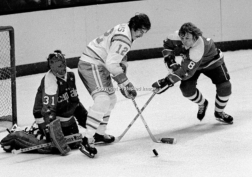 Seals Butch Williams tries to score on#8 Gord Smith and Washington goalie Michael Belhumeur, (1975 photo/Ron Riesterer)
