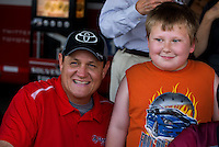 Aug. 31, 2013; Clermont, IN, USA: NHRA funny car driver Chad Head (left) poses for a photo with a fan during qualifying for the US Nationals at Lucas Oil Raceway. Mandatory Credit: Mark J. Rebilas-