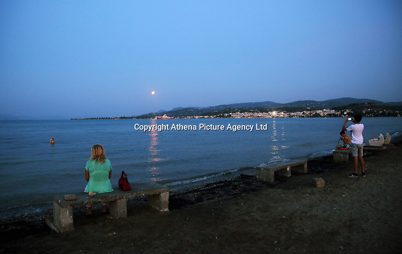 A full moon with a partial eclipse, rises over Oropos in the Evia Bay, 30 miles east of Athens, Greece. Monday 07 August 2017
