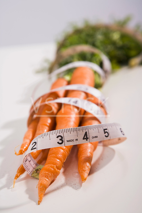 Tape measure wrapped around bunch of carrots
