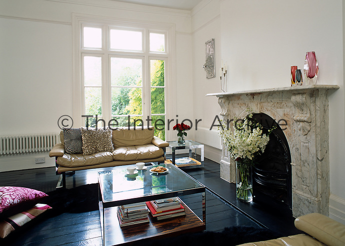 A pair of retro leather sofas and a glass-topped coffee table are arranged around a marble fireplace in the living room