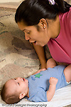 2 month old baby boy on back interested in interaction with mother vertical Hispanic Puerto Rican