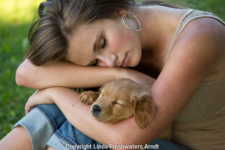 Young woman napping with a golden retriever puppy
