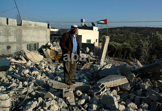Palestinians stand on the rubble of a house after it was demolished by Israeli army bulldozers in the village of Hares, near the West Bank city of Nablus, 14 April 2010. The house and some shops in the village were destroyed because they didn't have building license.  Photo by Nedal Shtieh