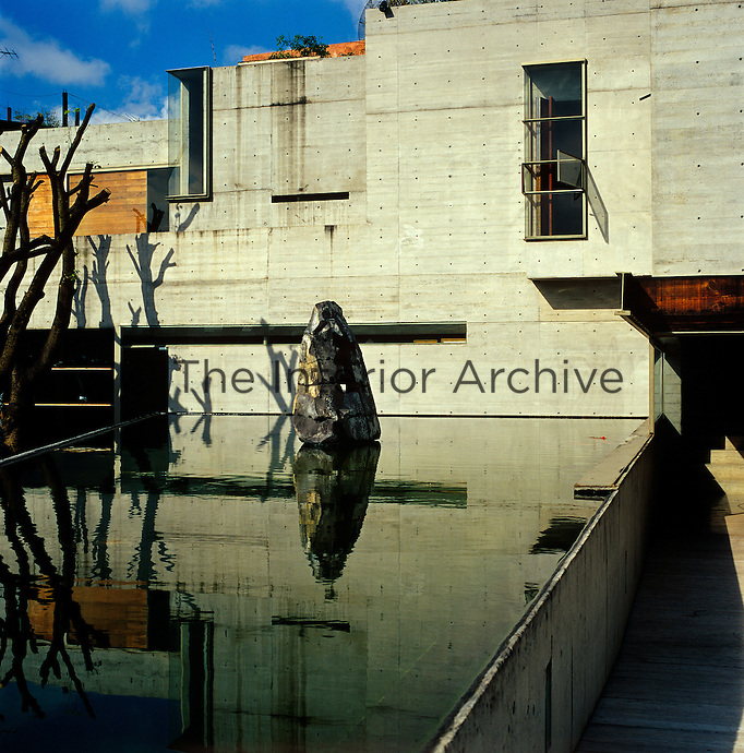 The rear facade of the house in reflected in the still water of the raised pool