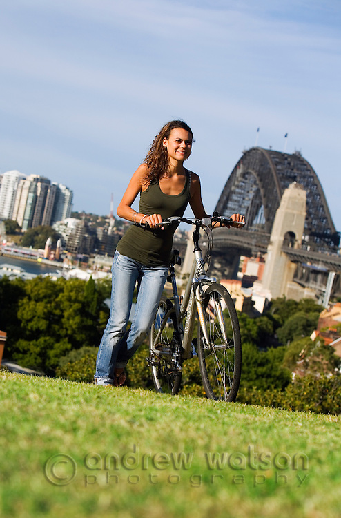 A woman pushes her bicycle up Observatory Hill overlooking Sydney harbour.  The Rocks,  Sydney, New South Wales, AUSTRALIA.