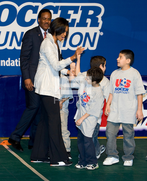 First Lady Michelle Obama high-fives a local student after a drill during a US Soccer Foundation clinic held at City Center in Washington, DC.