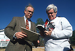 Powder Springs, Ga.: From left, Clive Rainey, Associate Director of Habitat for Humanity, gives Rep. Newt Gingrich (R-Ga.) a book on the organization at a Habitat for Humanity building site on Dec. 18, 1994, in Powder Springs, Ga.