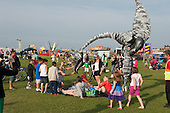 "Dynosaurs (saurus) walking amongst the crowd at ""Showtime"", part of the London 2012 Festival of Arts to celebrate the London Olympics.  A family fun spectacle including dance, painting, music, acrobatics and some large mobile dynosaurs walking amongst the crowd.  On Blackheath Common, Saturday August 4th and funded by the Mayor of London and Arts Council England."