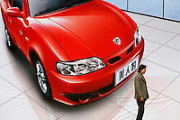 A man stands in front of an advertisement for a sports car made by Geely Auto in Shanghai, China. Geely is one of the major privately owned automobile manufacturer in China..