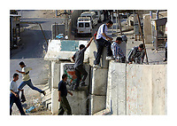 Palestinians cross the wall built to separate the Palestinian territories from Israel, June 1,2003, in the West Bank neighbourhood of Abu Deas, next to Jerusalem, as they return from illegal work in Israel. Photo by Quique Kierszenbaum
