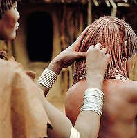 Hamer tribeswoman preparing hair with ochre, water and resin, to be twisted into tresses known as goscha, Turmi, Lower Omo Valley, Ethiopia