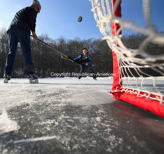 Middlebury, CT-01, January 2010-010110CM07 --  It was a father-son New Years moment on Turtle Pond in Middlebury Friday afternoon.  Sam Hamilton, 10 shoots the puck past his father, Alex, both of Middlebury, while playing ice hockey.  It's nice that we have our own pond to skate and play hockey on. It's almost as if it's our own private rink.  A lot of places you have to pay, and you can't play hockey on. This works out great. Alex Hamilton said.    Christopher Massa Republican-American