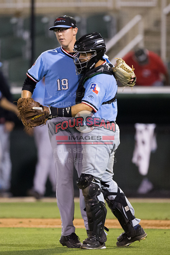 Hickory Crawdads relief pitcher Matt Ball (19) gets a hug from catcher Ricardo Valencia (15) after closing out the win over the Kannapolis Intimidators at Kannapolis Intimidators Stadium on May 18, 2017 in Kannapolis, North Carolina.  The Crawdads defeated the Intimidators 6-4.  (Brian Westerholt/Four Seam Images)