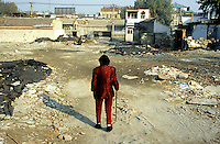 CHINA. Beijing. A woman walks amongst the ruins of an old hutong (traditional home) in the central Qianmen district, destroyed to make may for new developments aimed at modernising the city for the 2008 Summer Olympics. 2005