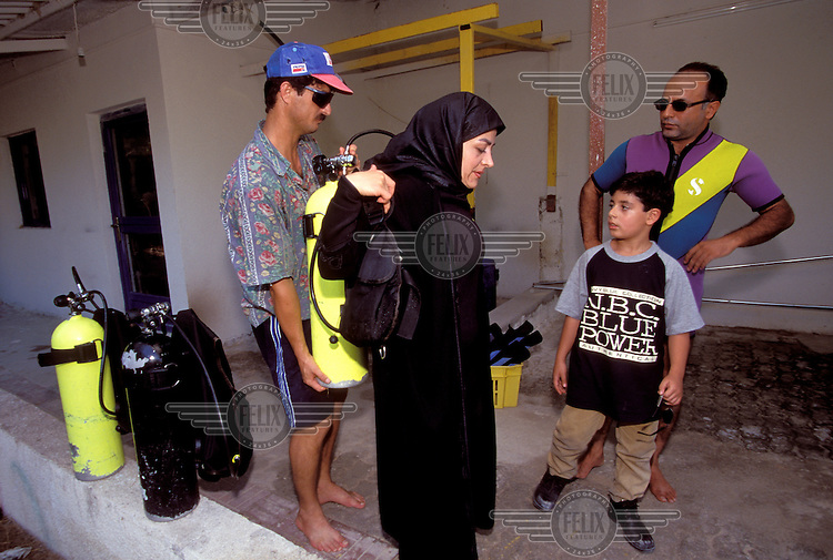 © Caroline Penn / Panos Pictures..Iranian women in sport..Kish Island, Iran. October 1999...Husband and wife preparing for a scuba diving lesson on the holiday island of Kish in the Persian Gulf.