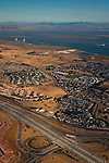 Aerial over tract housing, freeway, and Delta, near Bay Point, California