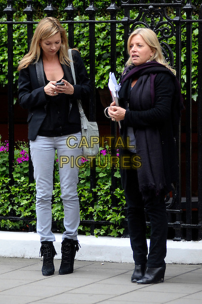 KATE MOSS.Outside Claridges Hotel, London, England..May 5th, 2010.full length black jacket top boots jeans denim text texting mobile phone .CAP/DYL.©Dylan/Capital Pictures.