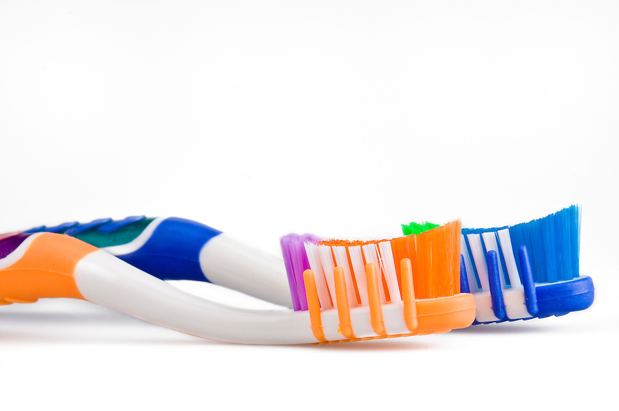 Close up of 2 toothbrushes over white background.
