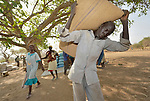 People receive food from the ACT Alliance on April 7, 2017, in Rumading, a village in South Sudan's Lol State where more than 5,000 people, displaced by drought and conflict, remain in limbo. In early 2017, they set out walking for Sudan, seeking better conditions, but were stopped from crossing the border. They remain camped out under the trees at Rumading, eating wild leaves as the rainy season approaches. <br /> <br /> In early April, Norwegian Church Aid, a member of the ACT Alliance, began drilling a well in the informal settlement and distributed sorghum, beans and cooking oil to the most vulnerable families. The man, a resident of a nearby community who will receives a handful of food for his work, carries a 100 kilogram bag of sorghum that will be divided between several vulnerable families. <br /> <br /> The ACT Alliance is carrying out the emergency assistance in coordination with government officials and the local Catholic parish.