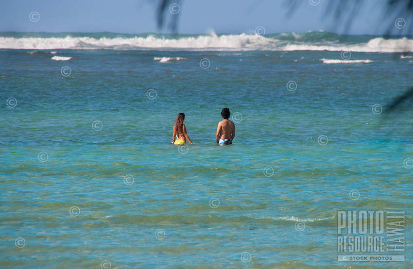 A young couple enjoying the ocean off Haena Beach Park, North Shore, Kauai.
