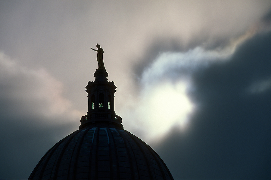 The Wisconsin statue atop the dome of the Wisconsin State Capitol is silhouetted against the sun breaking through the clouds in downtown in Madison, Wis., during winter 2002. (Photo by Jeff Miller - www.jeffmillerphotography.com)