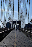Image shows the patterns made by the Brooklyn Bridge's support wires against a blue clouded sky and the shadow on the bridge's wooden walkway. The American flag flies from atop the bridge's central arches.