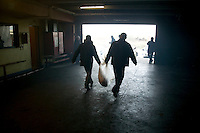 Two men carries away a carcass of a freshly slaughtered sheep at a temporary slaughterhouse set up in an hanger in Pantin, outside Paris, France, 1 February 2004, during the ritual sheep slaughter held for the Muslim celebration of Aid-el-Kebir. Photo Credit: David Brabyn.