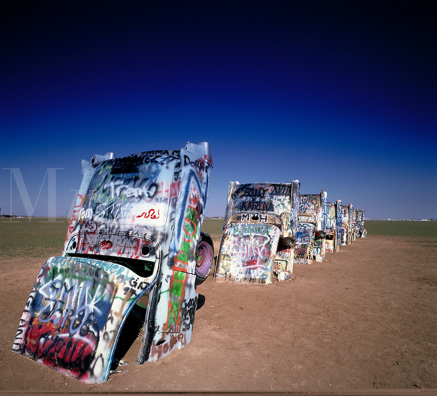 The famous Cadillac Ranch with its half-buried Cadillacs, which are now coated with spray-painted designs and graffiti. Amarillo, Texas.