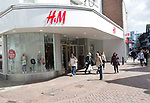H & M shop shoppers walking in street, Tavern Street, Ipswich, Suffolk, England, UK