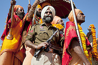 India. Uttar Pradesh state. Allahabad. Maha Kumbh Mela. A Sikh man working for a private security firm is looking after a guru's security. He holds a submachine gun in his hands and stands close to the guru. The Kumbh Mela, believed to be the largest religious gathering is held every 12 years on the banks of the 'Sangam'- the confluence of the holy rivers Ganga, Yamuna and the mythical Saraswati. The Maha (great) Kumbh Mela, which comes after 12 Purna Kumbh Mela, or 144 years, is always held at Allahabad. Uttar Pradesh (abbreviated U.P.) is a state located in northern India. 7.02.13 © 2013 Didier Ruef