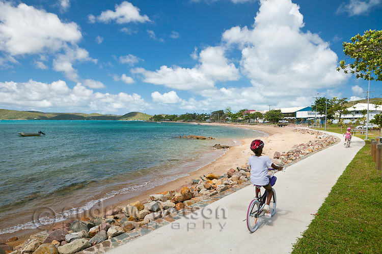 Kids ride their bikes along the Victoria Parade esplanade.  Thursday Island, Torres Strait Islands, Queensland, Australia