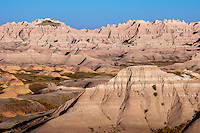 Badlands National Park is a&nbsp;in southwestern&nbsp;South Dakota&nbsp;that protects 242,756 acres&nbsp;of sharply&nbsp;eroded&nbsp;buttes, pinnacles, and spires blended with the largest undisturbed mixed&nbsp;grass&nbsp;prairie&nbsp;in the United States. <br /> <br /> These striking geologic deposits contain one of the world&rsquo;s richest fossil beds. Ancient mammals such as the rhino, horse, and saber-toothed cat once roamed here. The park&rsquo;s 244,000 acres protect an expanse of mixed-grass prairie where bison, bighorn sheep, prairie dogs, and black-footed ferrets live today.<br /> <br /> The Lakota people were the first to call this place &quot;mako sica&quot; or &quot;land bad.&quot; Extreme temperatures, lack of water, and the exposed rugged terrain led to this name. In the early 1900's, French-Canadian fur trappers called it &quot;les mauvais terres pour traverse,&quot; or &quot;bad lands to travel through.&quot;<br /> <br /> Today, the term badlands has a more geologic definition. Badlands form when soft sedimentary rock is extensively eroded in a dry climate. The park's typical scenery of sharp spires, gullies, and ridges is a premier example of badlands topography.