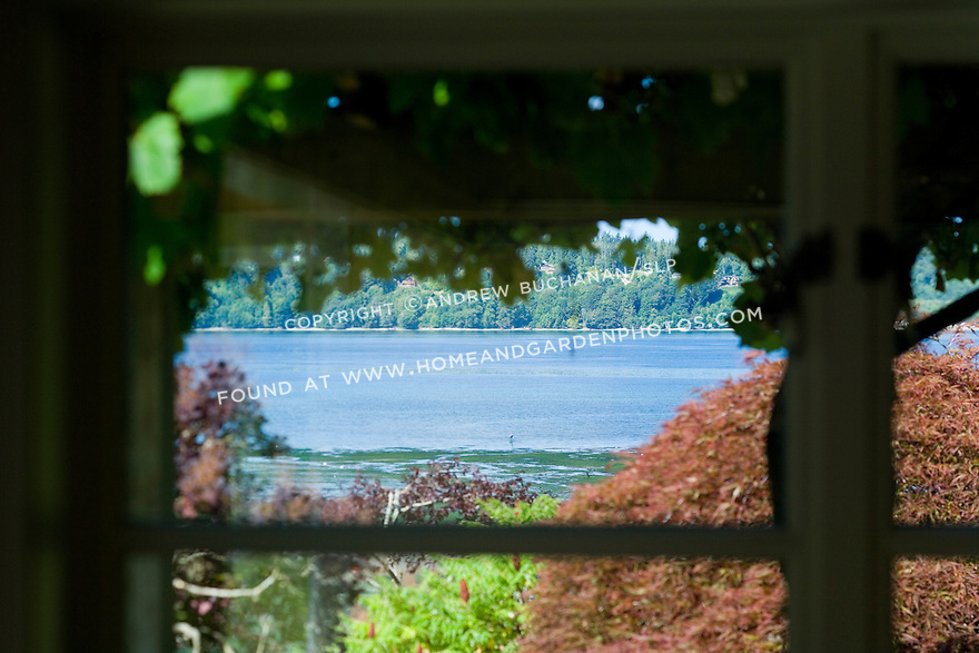 Close-up detail of the view of the deep blue salt water through a white-painted window frame in soft foreground focus in this waterfront weekend vacation retreat on Washington State's Vashon Island.