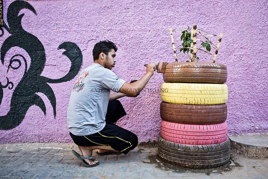 GAZA, Zaytoun: A young man  from the Zaytoun neighbourhood is painting tires used as decoration in the street.  14/08/15<br /> <br /> GAZA , Zaytoun : Un jeune homme du quartier de Zaytoun peint des pneus utilis&eacute;s comme d&eacute;coration dans la rue. 14/08/15