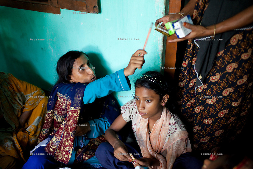 Jesmin Akhter, 26 (in turquoise & blue), sells her products in one of her 'marketplaces', Jerai Villlage, Gobindagonj Upazila, Gaibandha, Bangladesh on 19th September 2011. She has found financial independence and contributes to her household income by working as a saleswoman, earning 3500 - 5000 Bangladeshi Taka per month. She is the top saleswoman under her 'hub', out of 30 women. Having worked for about 2.5 years, she cycles from village to village and door to door in a country where women on bicycles is an extremely uncommon sight. She is one of many rural Bangladeshi women trained by NGO CARE Bangladesh as part of their project on empowering women in this traditionally patriarchal society. Named 'Aparajitas', which means 'women who never accept defeat', these women are trained to sell products in their villages and others around them from door-to-door, bringing global products from brands such as BATA, Unilever and GDFL to the most remote of villages, and bringing social and financial empowerment to themselves.  Photo by Suzanne Lee for The Guardian