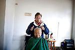 Business owner and barber, Charles Castillo, 61, cuts hair on Rogie Relova, 75, in Vallejo, Ca., on Wednesday, Feb. 10, 2010.  Castillo says he no longer goes to the grocery store at night for fear he could be accosted, and worries about the thinning of the police force due to budget cuts..