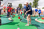 CROMWELL, CT. 19 June 2019-061919 - Emma Thistlewaite of New Hartford, center, putts the ball in the hole, with Sonar the mascot of the Hartford Wolfpack, left,  looking on during the Travelers Championship's Dunkin Celebrity Mini Golf Tournament at the TPC River Highlands in Cromwell on Wednesday. Bill Shettle Republican-American