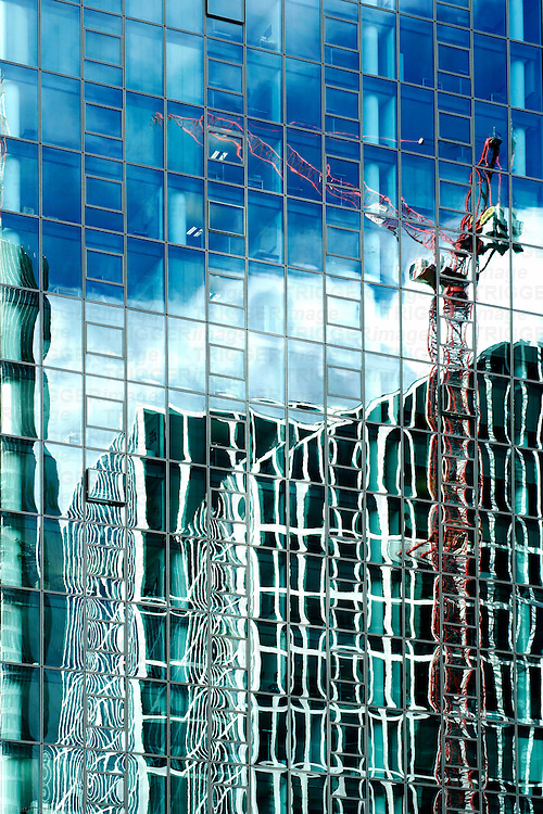 The photograph of a high-rise building facade with the reflection of scaffolding and a crane.