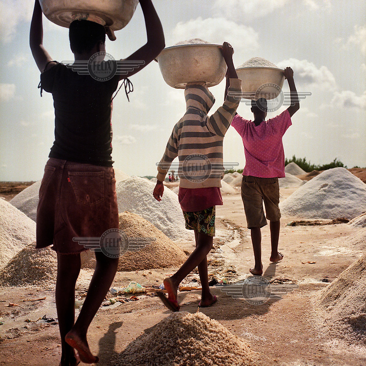People collect bowls of salt that forms in the lagoons around the town of Big Ada on the Volta Delta.