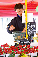 Street market merchant's stall with strawberries, a man weighing the fruit Sanary Var Cote d'Azur France