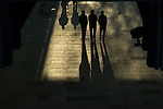 Silhouetted pedestrians in an underpass.