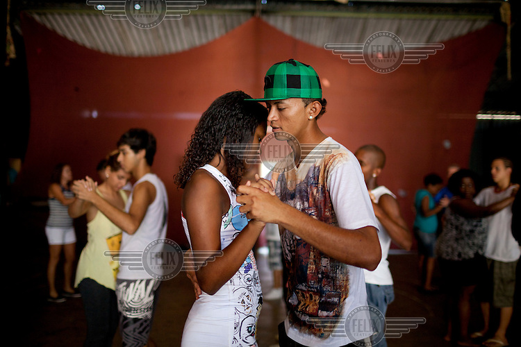 Residents taking a dance class in Complexo da Mare. The favela consists of a complex of 16 communities, in the north zone of Rio de Janeiro. It is the largest complex of favelas, housing 130,000 residents. It is targeted for pacification as the city prepares for the 2014 World Cup and the 2016 Olympics. Four factions run the complex, three drug gangs and the militia. The rival gangs fight for control of the drug trade. Although crime is low in the favelas by rule of law enforced by the gangs, cross-fire shootings and gang violence is often high. Neighborhood associations are an integral part of community development within Mare, making up for a lack of government assistance.